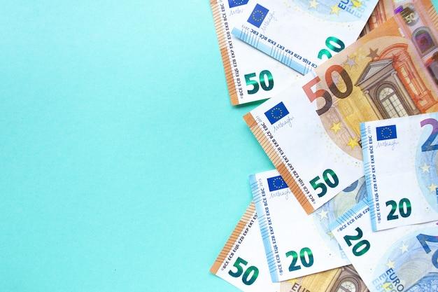 Банкноты достоинством 50 и 20 евро лежат на синем фоне с правой стороны. понятие денег и финансов. с местом для текста.