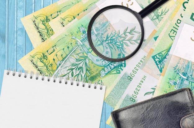 Банкноты 50 белорусских рублей и увеличительное стекло с черным кошельком и блокнотом. понятие о поддельных деньгах. поиск различий в деталях денежных купюр для обнаружения фальшивых денег