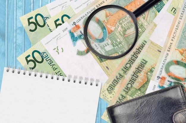 Купюры 50 белорусских рублей и увеличительное стекло с черным кошельком
