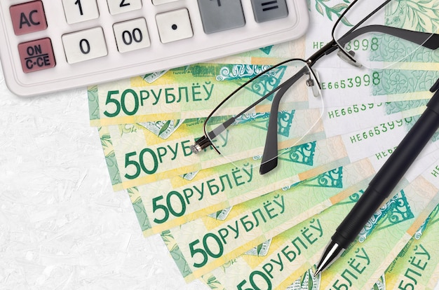 50 belorussian rubles bills fan and calculator with glasses and pen. business loan or tax payment season concept. financial planning