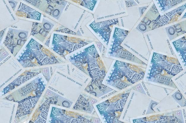 50 개의 크로아티아 쿠나 지폐가 큰 더미에 놓여 있습니다. 풍부한 생활 개념 벽. 많은 돈