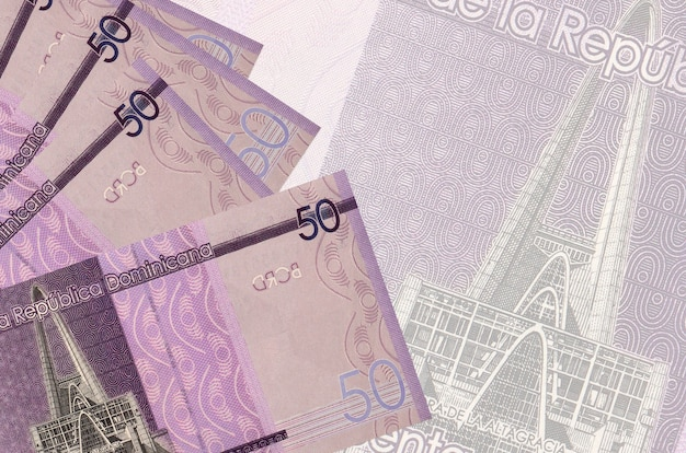 50 dominican pesos bills lies in stack on wall of big semi-transparent banknote. abstract business wall with copy space