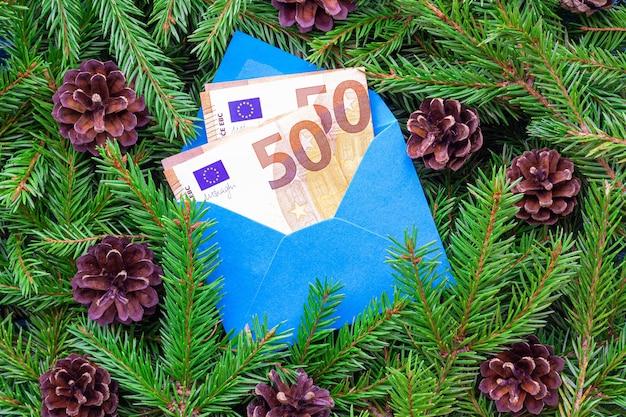 크리스마스 트리 분기의 배경에 파란색 봉투에 50 유로 지폐.