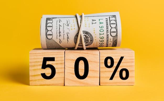 黄色の背景にお金で50の関心。ビジネス、金融、クレジット、収入、貯蓄、投資、交換、税金の概念