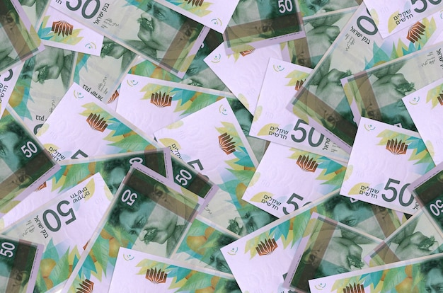 50 개의 이스라엘 새 세겔 지폐가 큰 더미에 놓여 있습니다. 풍부한 생활 개념 벽. 많은 돈