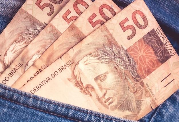 50 reais brazilian real banknotes inside a pants pocket in macro photography
