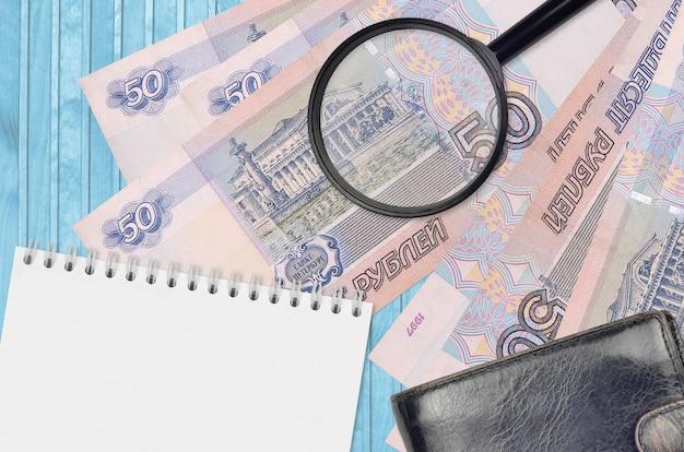 Купюры 50 российских рублей и увеличительное стекло с черным кошельком