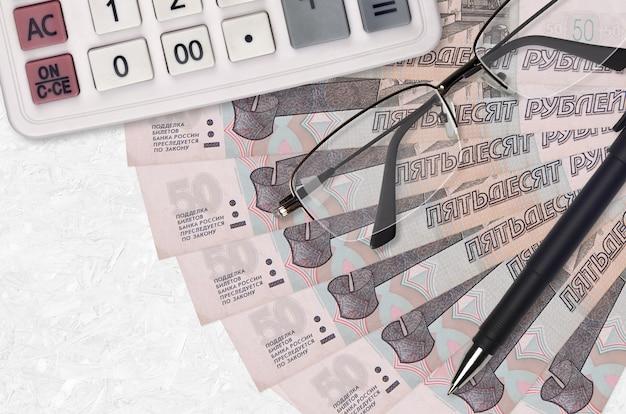 Вентилятор банкнот 50 российских рублей и калькулятор с очками и ручкой. бизнес-кредит или концепция сезона налоговых платежей