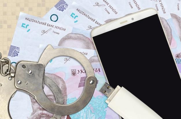 50ウクライナグリブナ紙幣と警察の手錠付きスマートフォン
