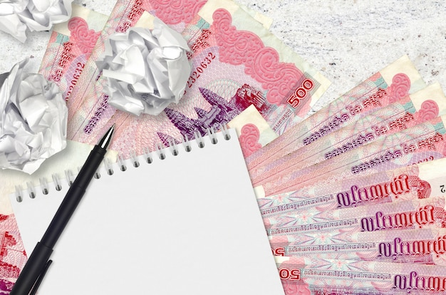 500カンボジアリエル手形と空白のメモ帳でしわくちゃの紙のボール。悪いアイデア以下のインスピレーションのコンセプト。投資のアイデアを探す