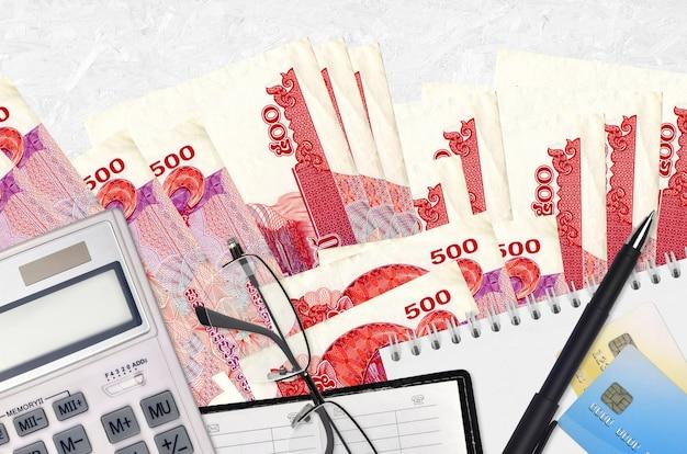 Банкноты 500 камбоджийских риелей и калькулятор с очками и ручкой.