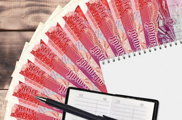 Вентилятор банкнот 500 камбоджийских риелей и блокнот с записной книжкой и черной ручкой. концепция финансового планирования и бизнес-стратегии. бухгалтерский учет и инвестиции