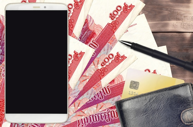 500 cambodian riels bills and smartphone with purse and credit card