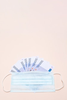 500 euro banknotes and a protective medical face mask on a light background