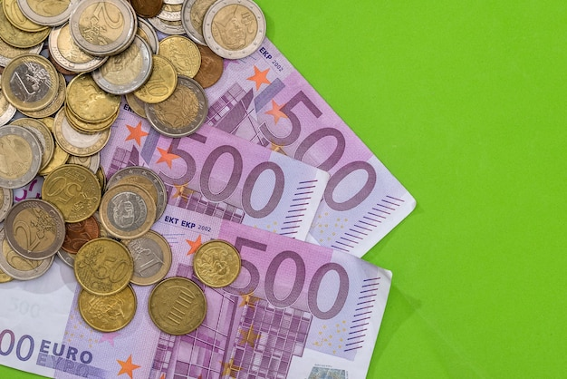 500 euro banknotes with coin on green