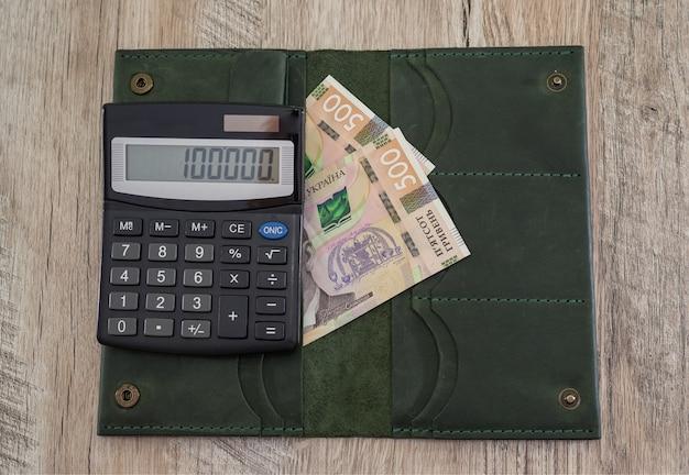 Женский кошелек 500 гривен и калькулятор на деревянном столе. финансовая концепция.