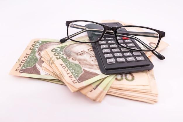 500 гривен с калькулятором и очками на белом фоне. финансовая концепция. украинские деньги.