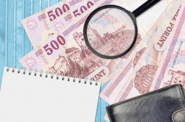 Банкноты 500 венгерских форинтов и увеличительное стекло с черным кошельком и блокнотом. понятие о поддельных деньгах. поиск различий в деталях денежных купюр для обнаружения фальшивых денег