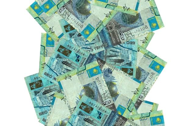500個のカザフスタンテンゲ紙幣が白で隔離されて飛んでいます。多くの紙幣が左右に白いコピースペースで落ちています