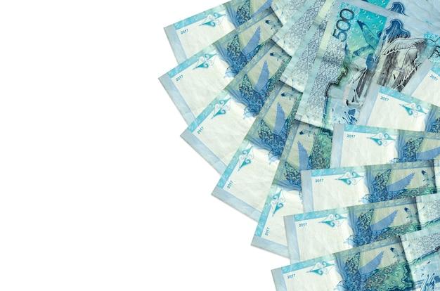 500のカザフスタンテンゲ手形はコピースペースのある白い壁に隔離されています。大量の自国通貨資産