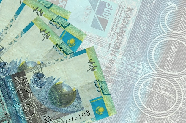 500 kazakhstani tenge bills lies in stack on wall of big semi-transparent banknote. abstract business wall with copy space
