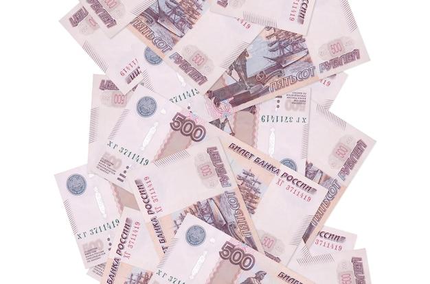 500ルーブルの請求書が白で隔離されて飛んでいます。多くの紙幣が左右に白いコピースペースで落ちています
