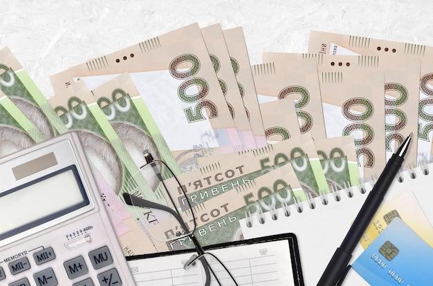 Банкноты 500 украинских гривен и калькулятор с очками и ручкой. концепция сезона налоговых выплат или инвестиционные решения