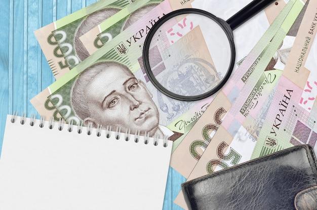 500 우크라이나 hryvnias 지폐와 검은 색 지갑과 메모장이있는 돋보기