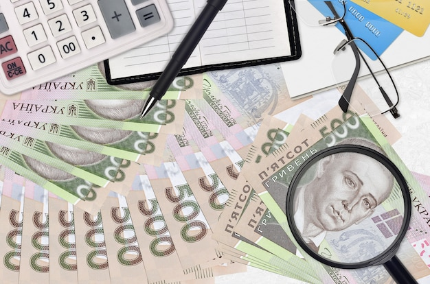 500 ukrainian hryvnias bills and calculator with glasses and pen. tax payment season concept or investment solutions.