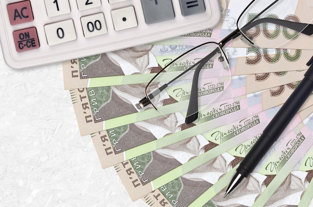500 ukrainian hryvnias bills fan and calculator with glasses and pen. business loan or tax payment season concept. financial planning