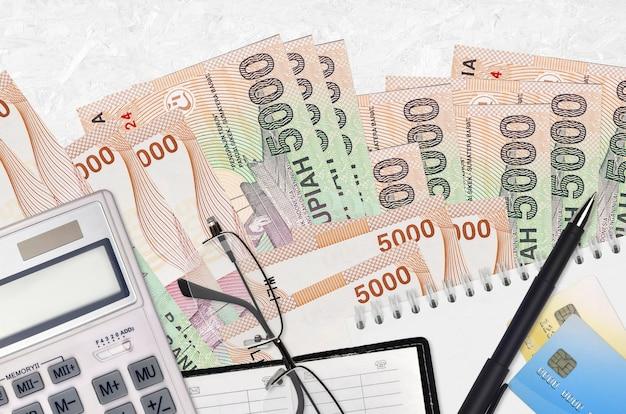 Банкноты 5000 индонезийских рупий и калькулятор с очками и ручкой