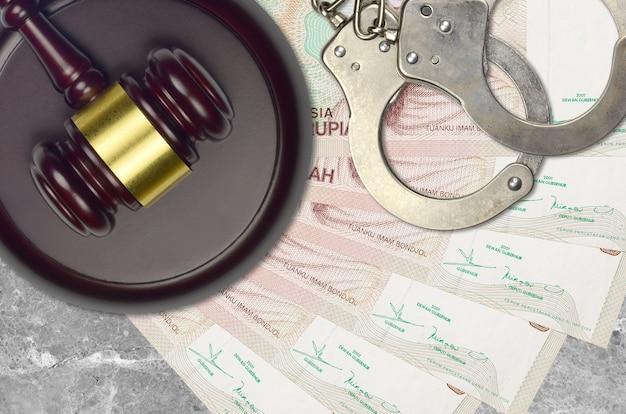 Банкноты в 5000 индонезийских рупий и молоток судьи с полицейскими наручниками на столе в суде. понятие судебного разбирательства или взяточничества. уклонение от уплаты налогов или уклонение от уплаты налогов