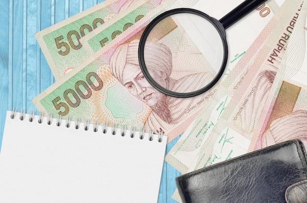 Банкноты 5000 индонезийских рупий и увеличительное стекло с черным кошельком и блокнотом