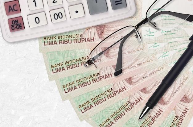 Вентилятор банкнот 5000 индонезийских рупий и калькулятор с очками и ручкой