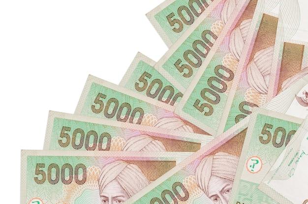 Банкноты 5000 индонезийских рупий лежат в разном порядке, изолированные на белом. местное банковское дело или концепция зарабатывания денег.