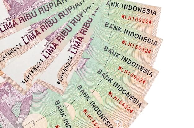 Банкноты 5000 индонезийских рупий лежат изолированно на белой стене с копией пространства, сложенными в форме вентилятора крупным планом. концепция финансовых операций