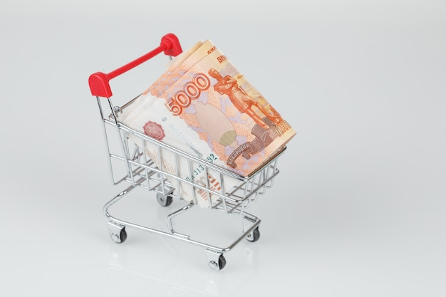 灰色の壁のショッピングカートで5000ロシアルーブル紙幣のコンセプト