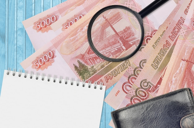 Банкноты 5000 российских рублей и увеличительное стекло с черным кошельком и блокнотом. понятие о поддельных деньгах. поиск различий в деталях денежных купюр для обнаружения фальшивых денег