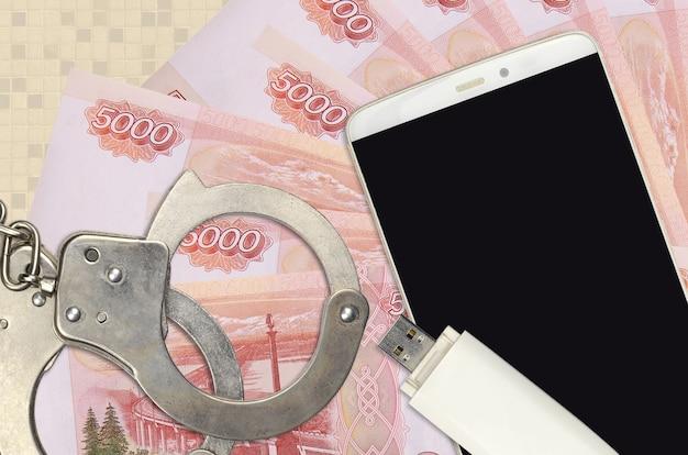 Купюры 5000 рублей и смартфон с полицейскими наручниками. концепция хакерских фишинговых атак, незаконного мошенничества или распространения шпионского программного обеспечения в интернете