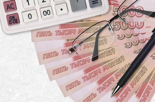Вентилятор банкнот 5000 российских рублей и калькулятор с очками и ручкой. бизнес-ссуды или концепция сезона уплаты налогов. финансовое планирование