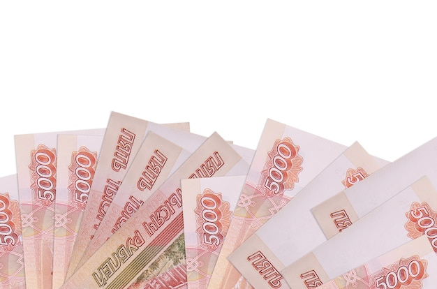 Купюры 5000 российских рублей лежат на нижней стороне экрана, изолированного на белой стене с копией пространства.