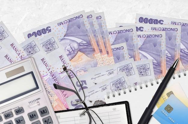 Банкноты 50000 румынских лей и калькулятор с очками и ручкой. концепция уплаты налогов или инвестиционные решения. финансовое планирование или бухгалтерские документы