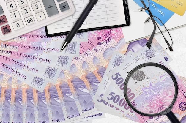 Банкноты 50000 румынских лей и калькулятор с очками и ручкой.