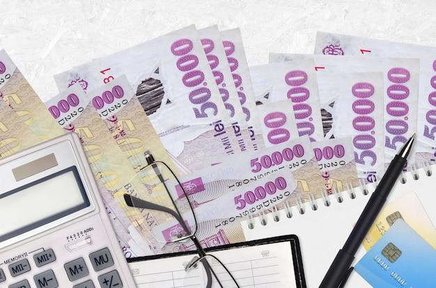 50000ルーマニアレウ紙幣とメガネとペンで電卓