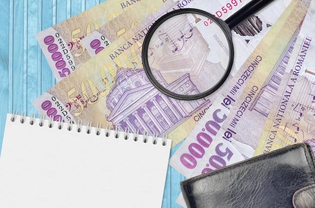 Банкноты 50000 румынских лей и увеличительное стекло с черным кошельком и блокнотом