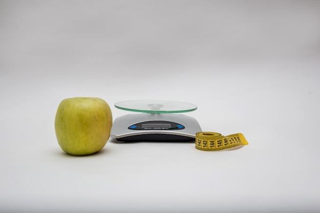Весы, яблоко и сантиметр на пустое пространство. копировать пространство на пустое пространство. весы показывают максимальный вес 5000 г, слова «мера» и «включить»