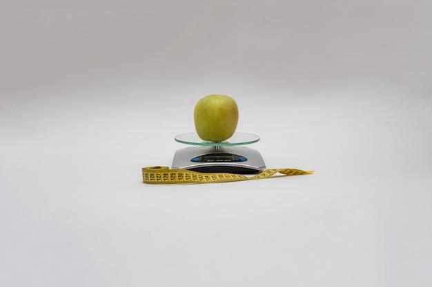 На кухонных весах - яблоко, рядом с сантиметром на пустом месте. копировать пространство на пустое пространство. весы показывают максимальный вес 5000 г, слова «мера» и «включить»