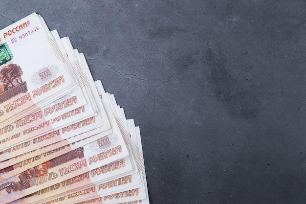 灰色のセメントの上に横たわる5000ルーブルのロシアのお金紙幣のビッグスタック。