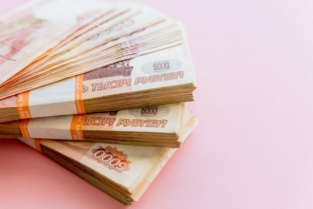 Стек пачек по 5000 рублей на розовом фоне