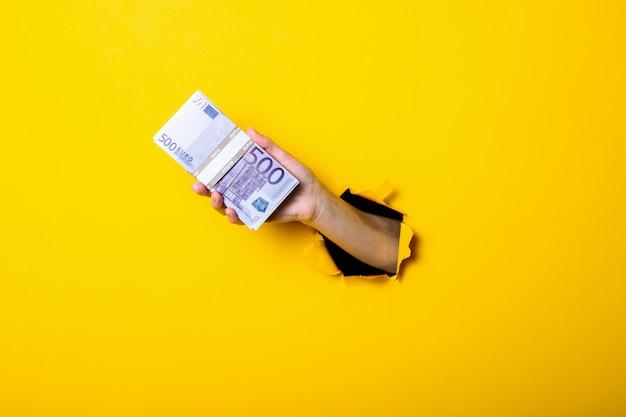 女性の手は500ユーロ紙幣の束を持っています